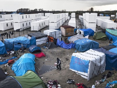 epa05095992 A migrant walks among the tents and huts of the makeshift camp called 'The Jungle' next to the fenced area made of containers recycled in rooms to host some 1,500 migrants in Calais, France, 10 January 2016. A new area of the camp will be inaugurated on 11 January as containers recycled as rooms will host its first occupants. Only half of a capacity of 1,500 places will be filled during the days. Between 4,000 and 7,000 migrants are currently living in 'The Jungle'.  EPA/ETIENNE LAURENT
