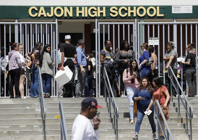 Parents and guardians of North Park Elementary School students wait at Cajon High School to pick up their children Monday, April 10, 2017, in San Bernardino, Calif. A deadly shooting occurred at the elementary school. (AP Photo/Jae C. Hong)